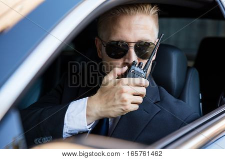 Surveillance Man Sitting Inside Car Talking On Walkie Talkie