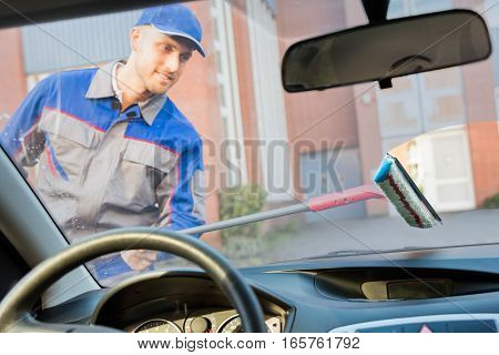 Happy Young Man Washing Car Window With Mop