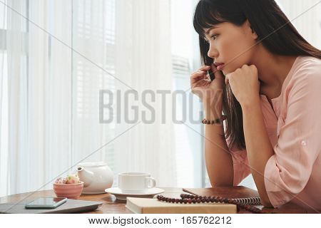 Asian young woman drinking tea and contemplating