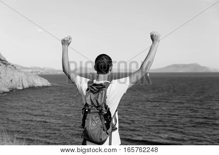 Black and white photo of man with backpack on sea background