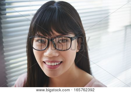 Face of Vietnamese smiling young woman in glasses