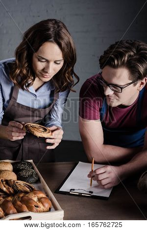 Male and female bakers examining pastries and making notes in bakery