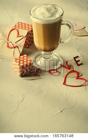 Coffee Latte with gift boxes, envelope and paper hearts. Pink, red, white colors on bright background. Love, Valentine's day concept. Copy space, vertical, toned