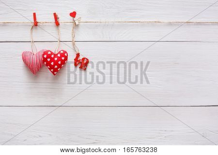Valentine background with sewed pillow diy handmade hearts couple on red clothespins at rustic white wood planks. Happy lovers day card mockup, copy space
