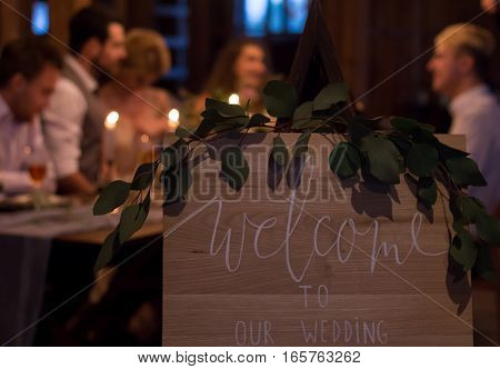 Wedding feast. Guests sit at festively decorated table. Evening candlelight.