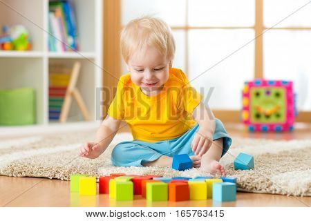 Child boy playing toy blocks inside his house