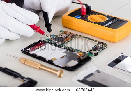 Close-up Of Person's Hand Checking Mobile Phone With Digital Multimeter