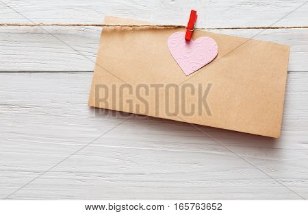 Valentine background, empty craft paper greeting card on clothespin on white rustic wood planks. Happy lovers day card mockup, copy space