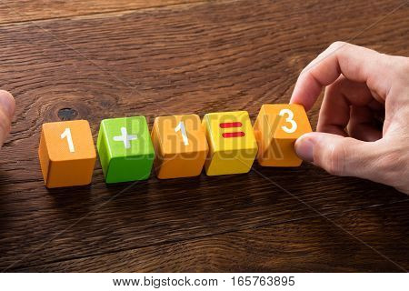 Close-up Of A Mathematical Equation On Colorful Block At Wooden Desk