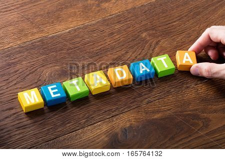High Angle View Of A Person With Metadata Concept On Colorful Block At Wooden Desk