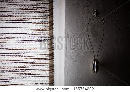 Close up shot of a curtain holder on a wall.