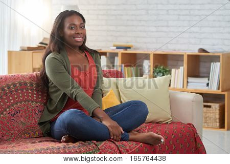 Beautiful woman sitting on sofa in her living room