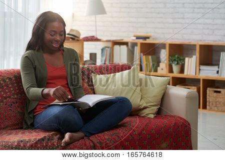 Pretty African-American woman sitting on sofa and reading magazine