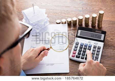 High Angle View Of A Auditor Hand Calculating Invoice Using Calculator On Desk. Tax Scrutiny And Fraud Investigation Concept