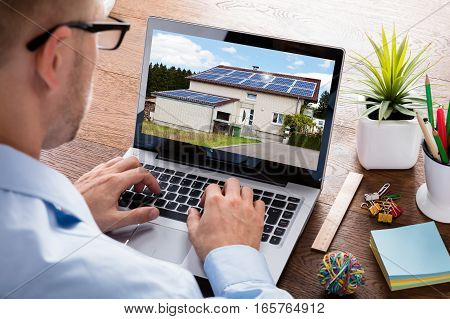 Close-up Of A Businessman Looking At Photo Of A House Online On Laptop Computer