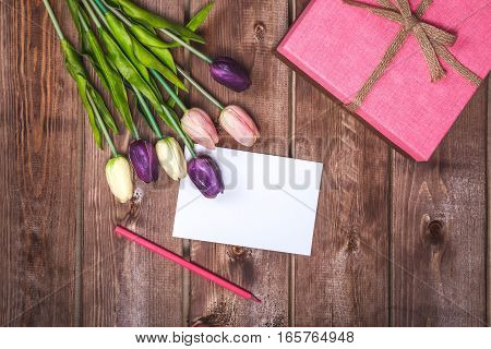 Romantic and pink Valentine's day decoration with present and DIY love card. Beautiful bouquet of purple tulips and card on wooden background.  Mothers day card .On March 8 is Women's Day