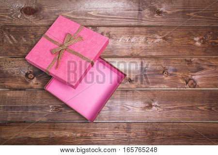 Wrapped vintage open pink gift box  on wooden background can use on valentine day mother day or celebrate love day .
