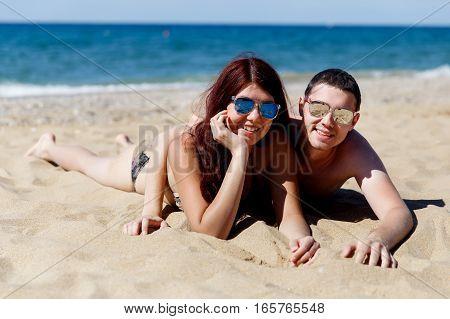 Girl with guy hugging lying on beach