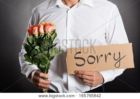 Man Holding Roses And Text Sorry Written On Cardboard Against Grey Background