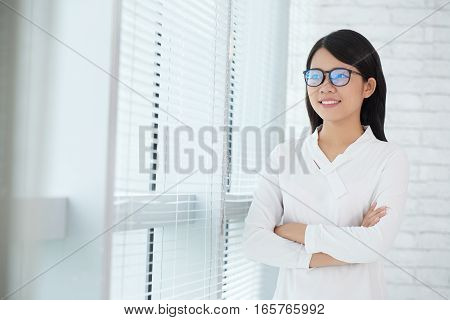 Pretty business executive in glasses standing with her arms crossed