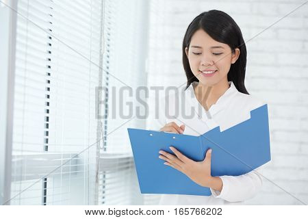 Smiling business lady checking documents in folder