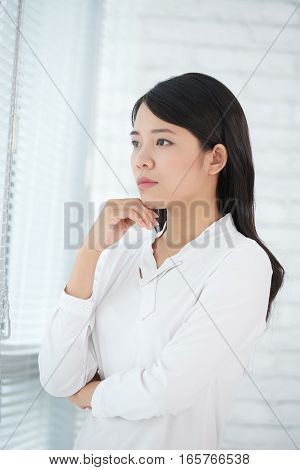 Potytait of young female business executive contemplating