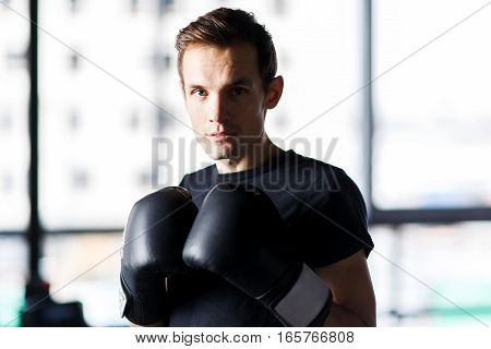 Portrait of boxer with boxing gloves in gym