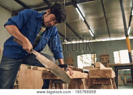 Asian carpenter sawing a wooden plank in workshop