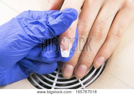 Manicure specialist care by finger nail in beauty salon.Gel nails. Finger closeup isolated on blue gloves background. Manicurist uses professional manicure tool.