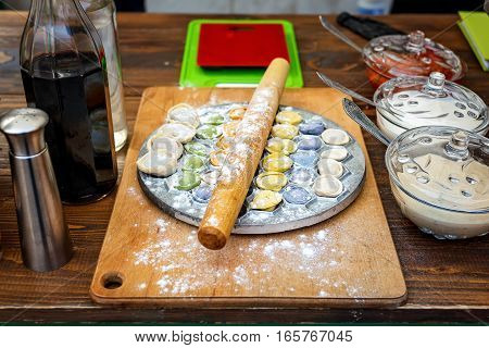 Meat dumplings russian pelmeni on wooden background with rolling pin