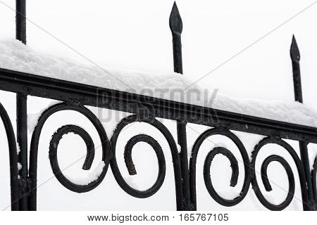 Black metal fence closeup. Snow on fence