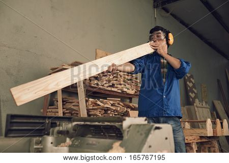 Carpenter checking in the board is flat and even