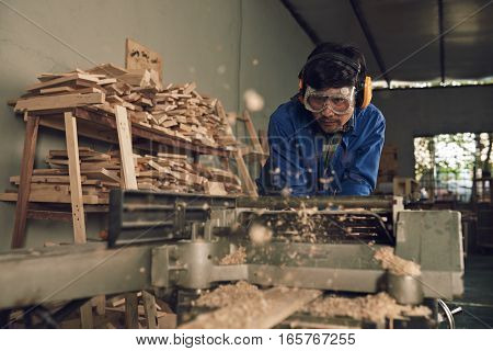 Professional carpenter using electric planer to make perfect planks