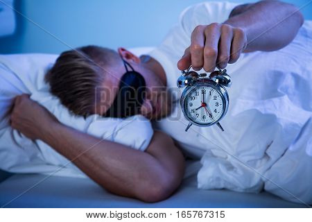 Man Sleeping On Bed By Holding Alarm Clock In His Hand