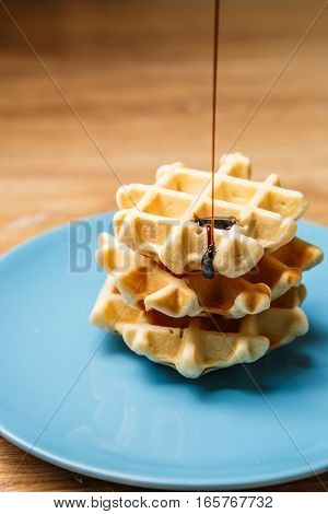 Homemade waffles sprinkles chocolate on blue plate