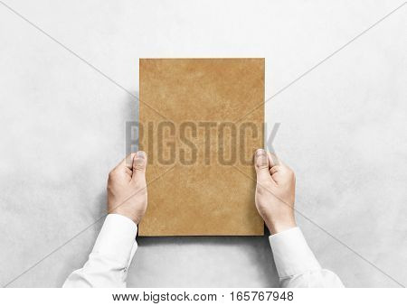 Hand holding kraft blank paper sheet mockup, isolated. Arm in shirt hold craft brochure template mock up. Leaflet document surface design. Simple brown print display show.