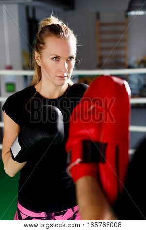 Blonde engaged in boxing with trainer in sports hall