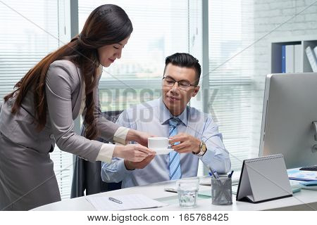 Female assistant bringing fresh coffee to entrepreneur