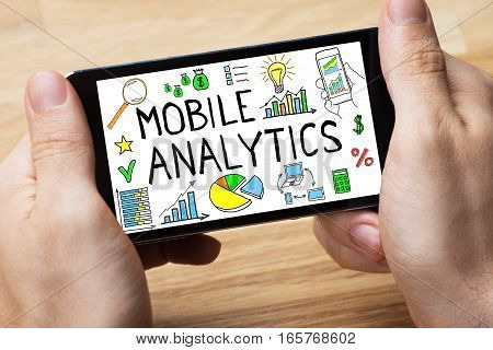 Close-up Of Person Hand Holding Mobilephone Showing Mobile Analytic Concept Online On Wooden Desk In Office