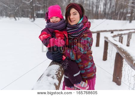 Woman holds little daughter in winter park