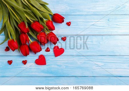 Red tulips and hearts on blue wooden table. Top view with copy space