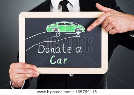 Close-up Of Businessman Showing Car Donation Concept On Slate At Grey Background