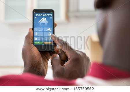 Close-up Of African Man Using Home Control System On Mobilephone