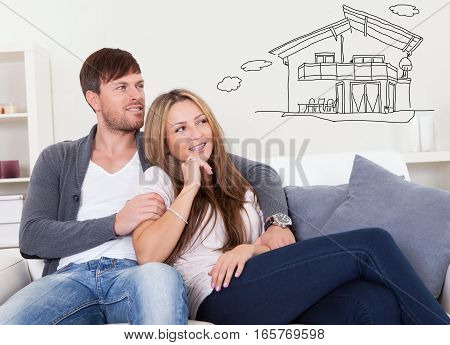 Young Thoughtful Couple Sitting On Sofa Thinking Of Getting Their Own House