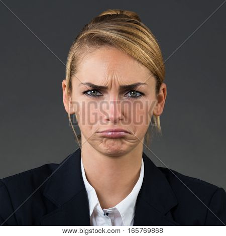 Portrait Of Young Unhappy Businesswoman On Grey Background