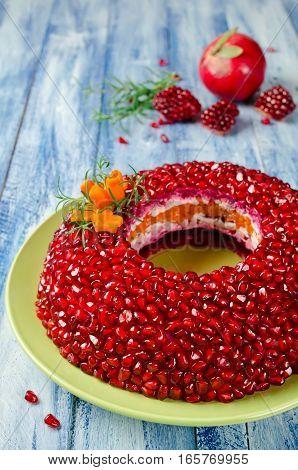 Salad Garnet bracelet on a wooden table. Vegetable salad with pomegranate seeds