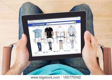 High Angle View Of Person Shopping Online On Digital Tablet At Home
