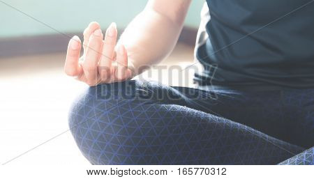 Young healthy woman yoga indoor. Close-up beautiful hand