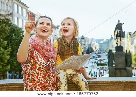 Mother And Child Travellers In Prague Holding Map And Pointing