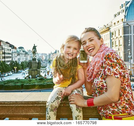 Mother And Daughter Travellers In Prague Speaking On Smartphone